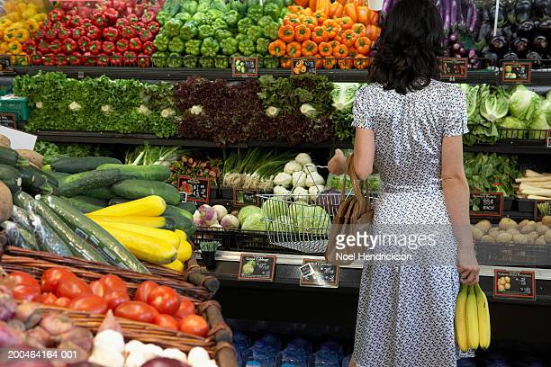 woman holding bananas in produce aisle of supermarket, rear view - produce aisle stock photos and pictures