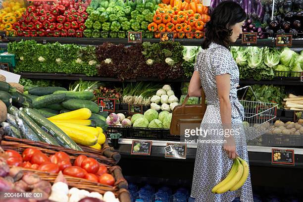 Woman holding bananas in produce aisle of supermarket, side view