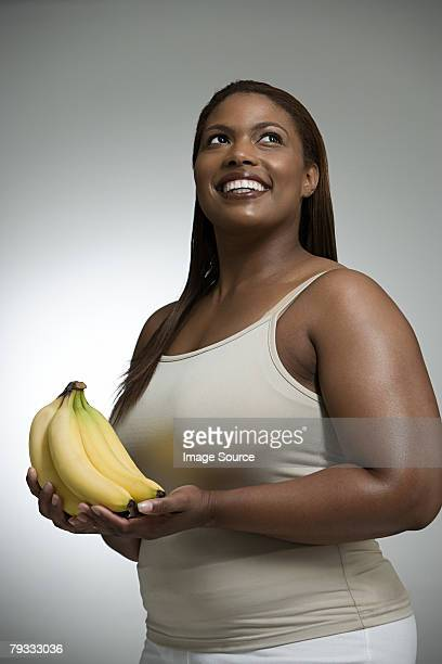 woman holding bananas - voluptuous black women stock photos and pictures