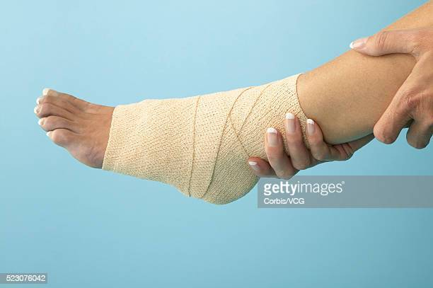 woman holding bandaged ankle - elastic bandage stock photos and pictures