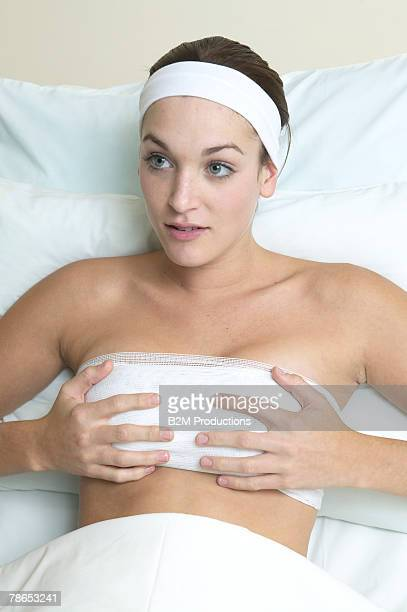 Woman holding bandaged breasts