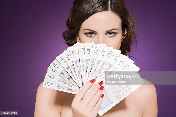 woman holding banknotes - twenty pound note stock photos and pictures
