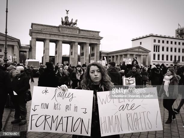 woman holding banners with crowd against brandenburg gate - marsch stock-fotos und bilder