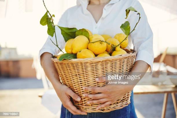 woman holding basket full of lemons - harvest basket stock pictures, royalty-free photos & images