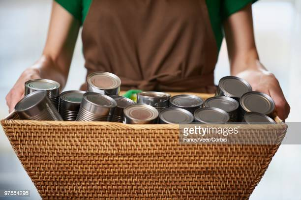 Woman holding basket of canned food
