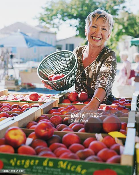 Woman holding basket of nectarines by fruit stall, smiling, portrait