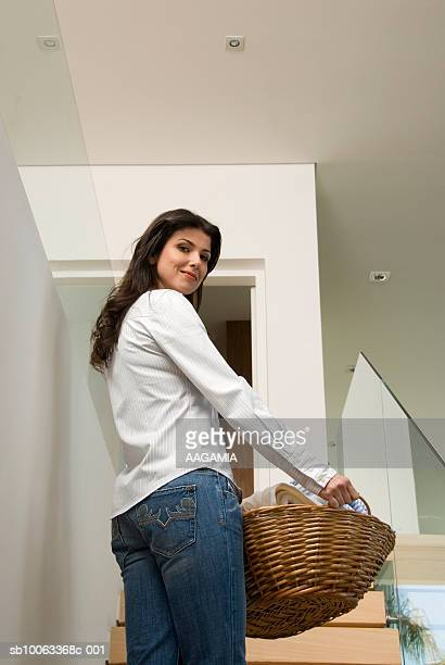 Woman holding basket, smiling, portrait, low angle view