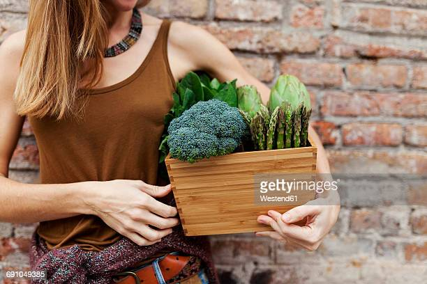 woman holding basket with fresh vegetables - cruciferae fotografías e imágenes de stock