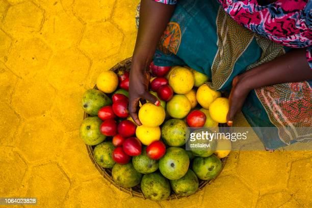 mujer con cesta de frutas tropicales en áfrica - ruanda fotografías e imágenes de stock