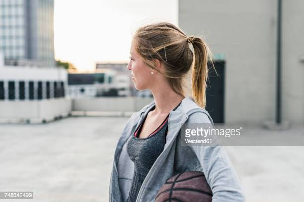 Woman holding basketball on parking level in the city