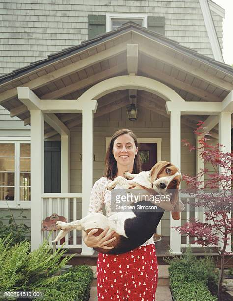 Woman holding basset hound in front of house, smiling, portrait
