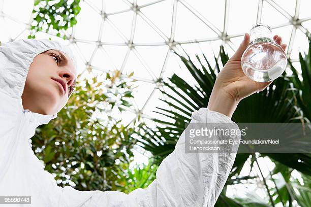 woman holding beaker in biosphere - ecologist stock pictures, royalty-free photos & images