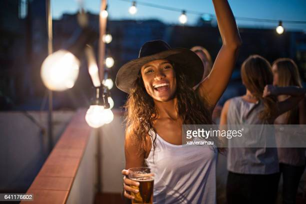 Woman holding beer glass while dancing on terrace