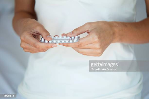 woman holding birth control pills, mid section - birth control pill stock pictures, royalty-free photos & images