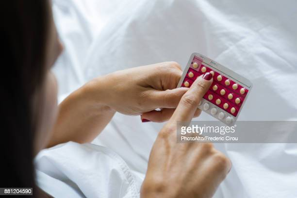 woman holding birth control pills - birth control pill stock pictures, royalty-free photos & images
