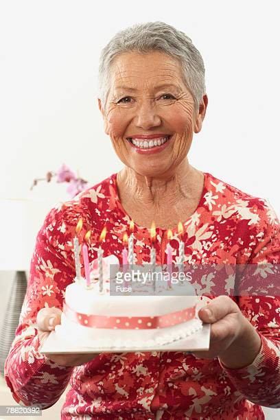 woman holding birthday cake - candle of hope stock pictures, royalty-free photos & images