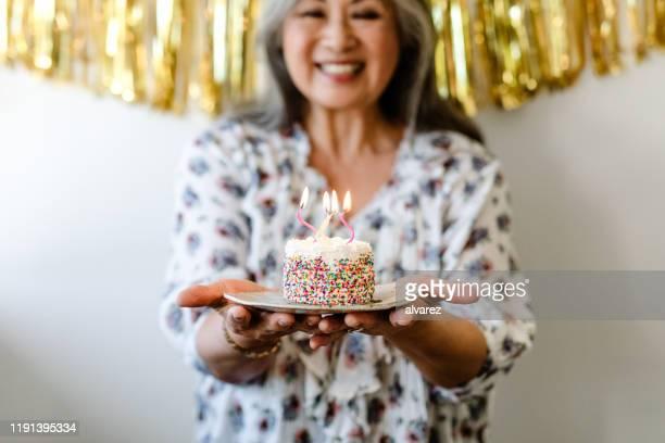 vrouw houdt verjaardagstaart met brandende kaarsen - 65 69 jaar stockfoto's en -beelden