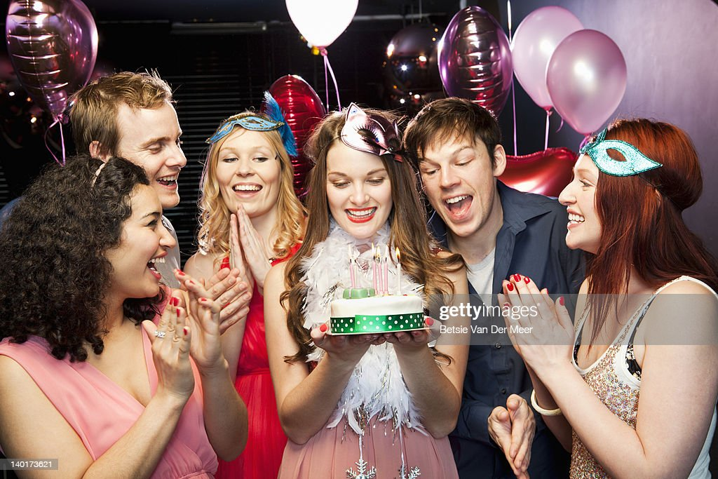 Woman holding birthday cake with friends around : Stock Photo