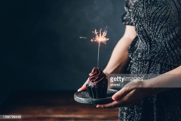 frau hält geburtstag kuchen mit feuerwerk kerze - geburtstag stock-fotos und bilder