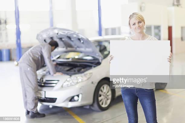 Frau holding leere Karte in der garage