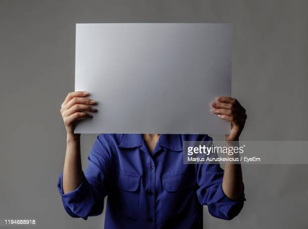woman holding blank paper against gray background - obscured face stock pictures, royalty-free photos & images