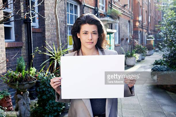 woman holding blank sign outside - person holding blank sign stock pictures, royalty-free photos & images