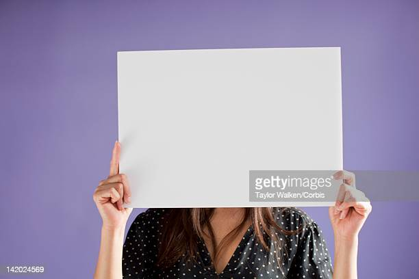 Woman holding blank white board over face