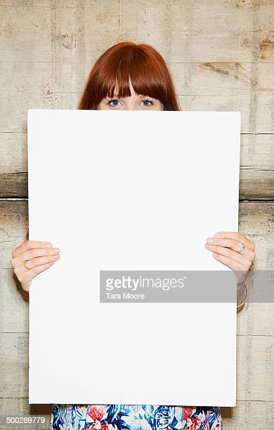 woman holding blank white message board
