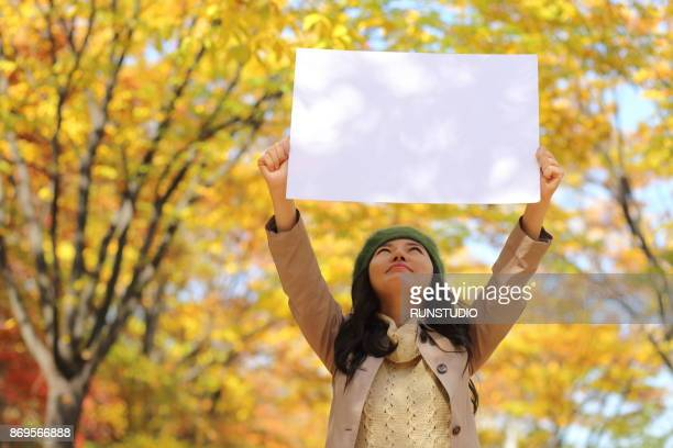 woman holding blank white sign in autumn park - holding aloft stock pictures, royalty-free photos & images