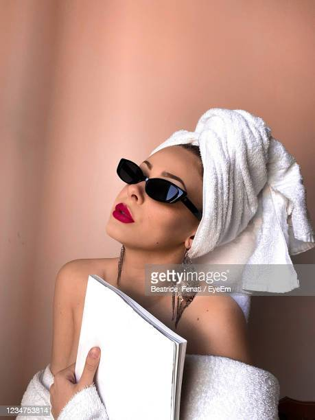 woman holding book against wall - beatrice stock pictures, royalty-free photos & images