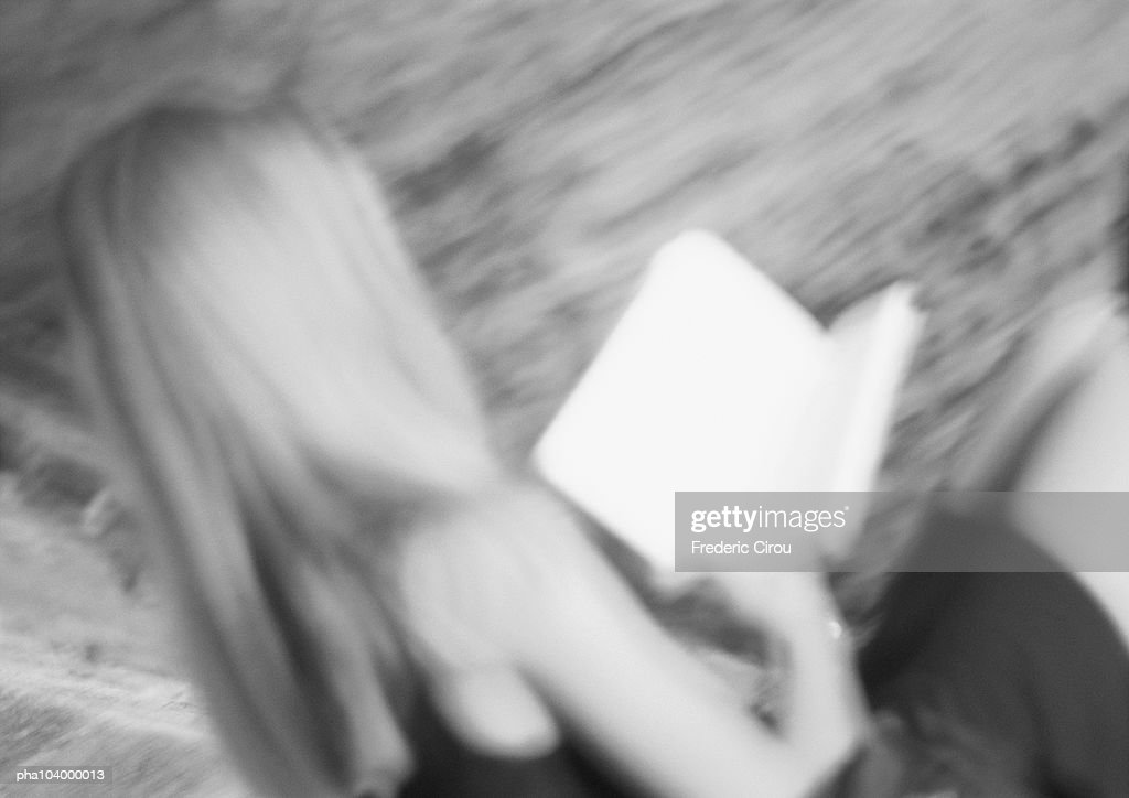 Woman holding book, blurred, b&w : Stockfoto