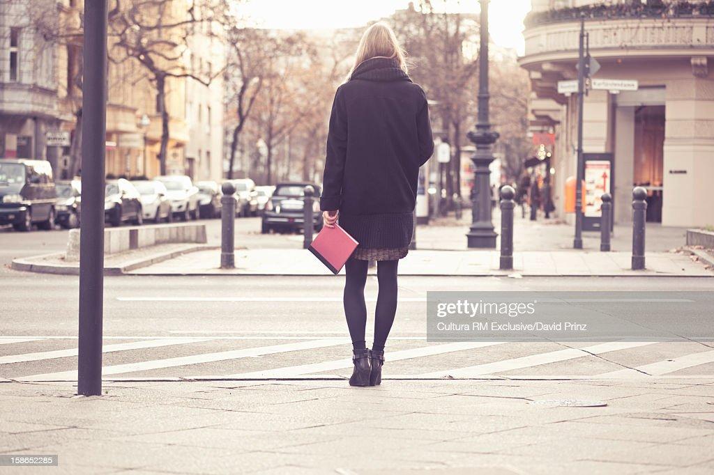 Woman holding book on city street : Stock Photo