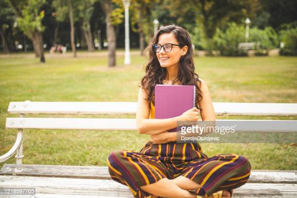 woman holding books and sitting on park bench - free business coaching stock pictures, royalty-free photos & images