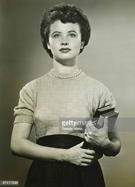 Woman holding books, posing in studio, (Portrait), (B&W)
