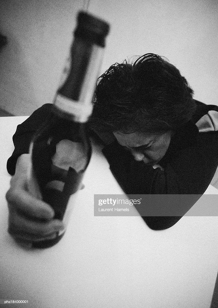 Woman holding bottle, leaning head on table, b&w : Stockfoto