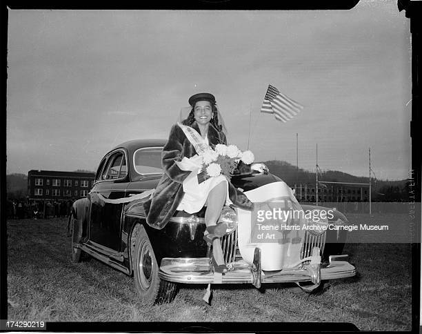 Woman holding bouquet and posed on car hood with Alpha Phi Alpha banner c 1946