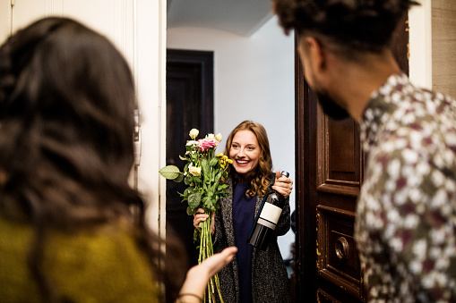 Woman holding bouquet and wine bottle while visiting friends - gettyimageskorea