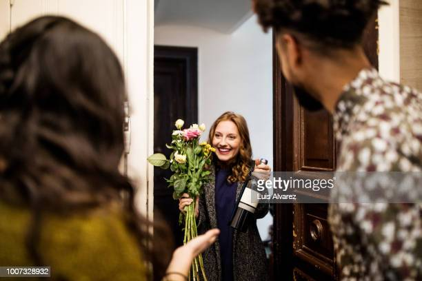 woman holding bouquet and wine bottle while visiting friends - bezoek stockfoto's en -beelden