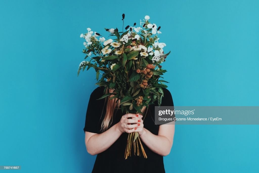 Woman Holding Bouquet In Front Of Face While Standing Against Blue Wall : Stock Photo