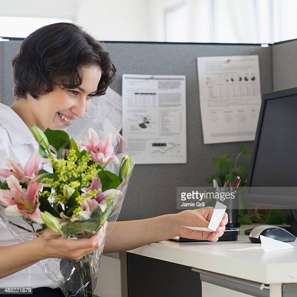 Woman holding bouquet in office