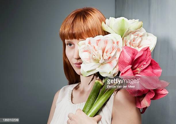 Woman holding bouquet of amaryllis flowers.