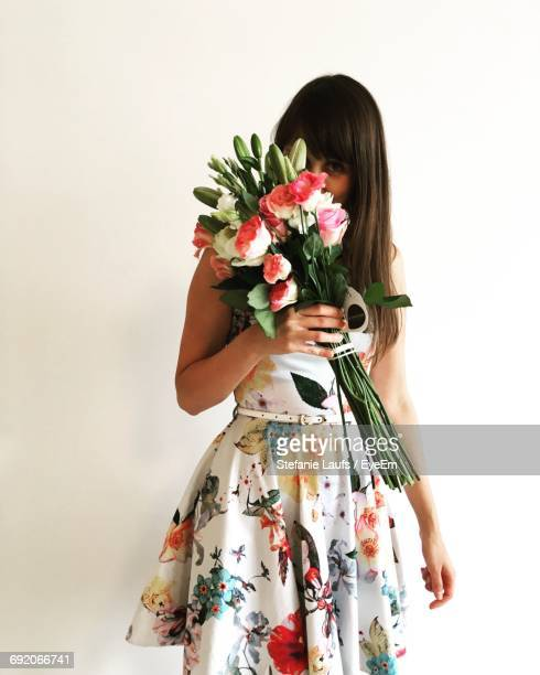 woman holding bouquet of flowers against white background - floral pattern dress stock pictures, royalty-free photos & images