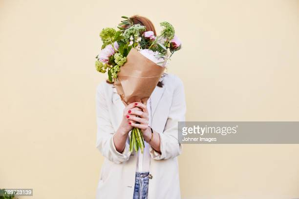woman holding bouquet of flowers - bloem stockfoto's en -beelden