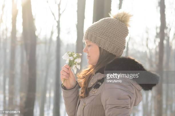 femme retenant le bouquet des perce-neige. profiter en hiver. - mois de mars photos et images de collection