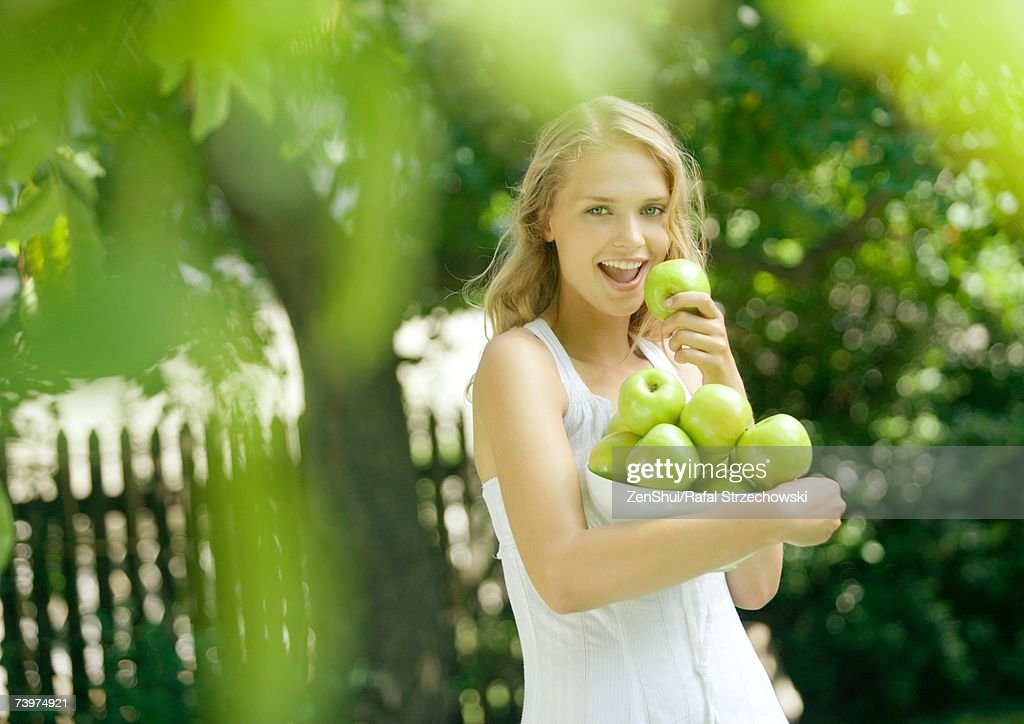 Woman holding bowl of apples, holding one up to mouth, smiling at camera : Stock Photo