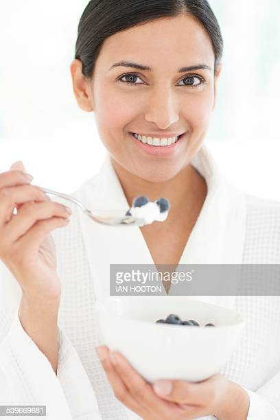 Woman holding bowl of fruit and spoon