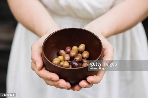 woman holding bowl of olives, mid section - parte mediana imagens e fotografias de stock
