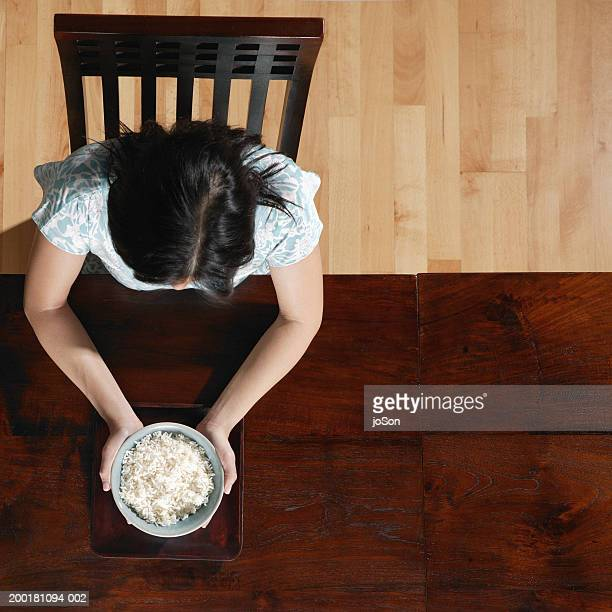 Woman holding bowl of white rice, overhead view