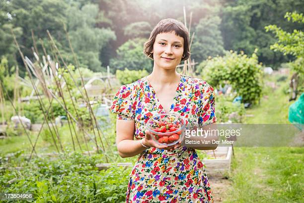 Woman holding bowl with picked strawberries.