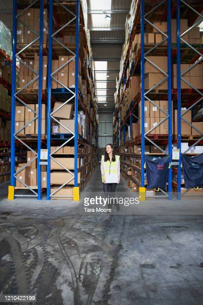 woman holding boxes in storage warehouse - femalefocuscollection stock pictures, royalty-free photos & images